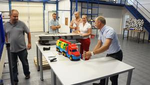 Foto mit fünf Personen und Modell-LKW