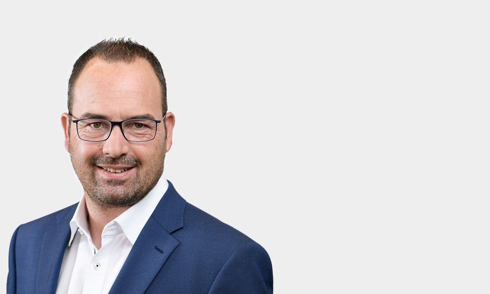 Portraetfoto von Gernot Schaefer vor grauem Hintergrund